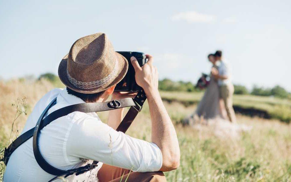 Photographe de mariage photographiant des mariés dans un pré