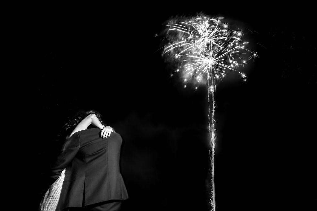 Les mariés s'enlacent sous un feu d'artifice, en noir et blanc
