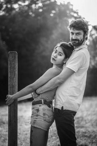 Couple s'enlaçant dans la lumière naturelle, en noir et blanc