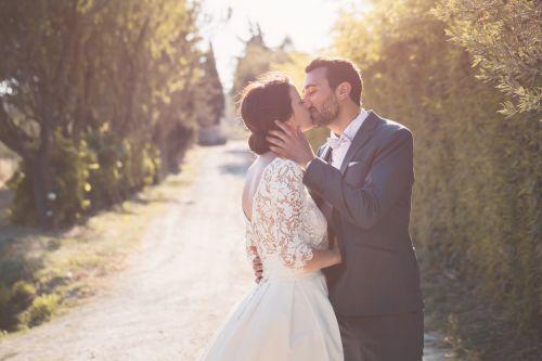 Mariés s'embrassant les yeux fermés en extérieur