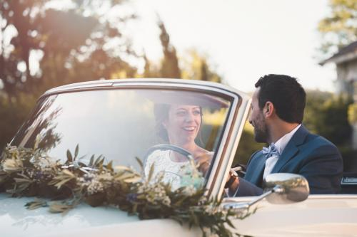 Mariés au volant d'une voiture décapotable, se regardant avec le sourire