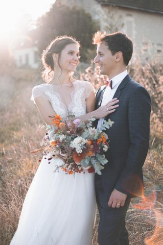 Couple de mariés avec bouquet dans la lumière du soir