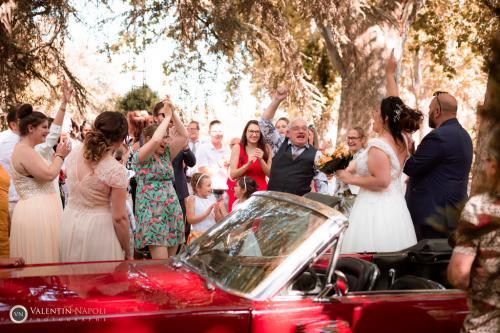 Les mariés, leur voiture, et les invités heureux