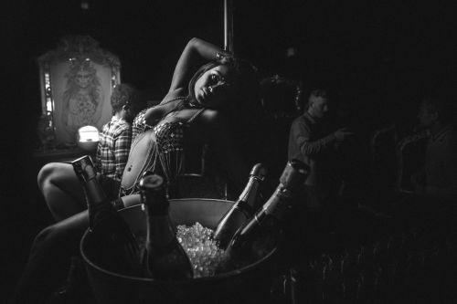 Danseuse dans un bar derrière des bouteilles de champagne