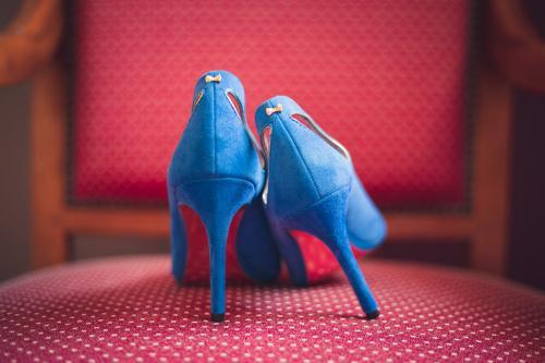 Escarpins bleus de la mariée, sur une chaise rouge