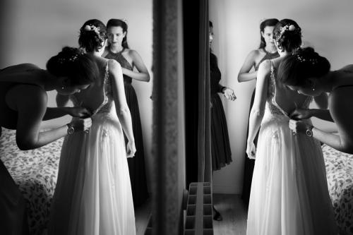 Mariée en plein préparatifs de sa robe, reflétée dans un miroir