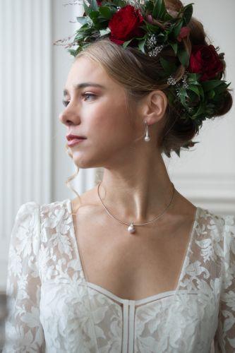 Mariée avec des bijoux en perle et une couronne de fleurs