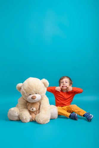 Portrait créatif d'un petit garçon et sa grosse peluche